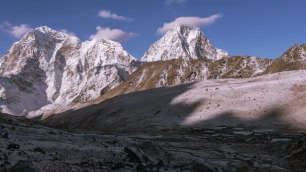 Turistický tábor na úpatí zasněžených vrcholů v Nepálu, pohoří Himaláje. Velkolepý pohled píku Cholatse (6440 m) a Taboche (6495 m) na pozadí modré oblohy při východu slunce. Časová prodleva