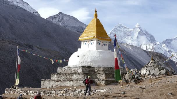 Taboche, Nepal - April, 2018: group of tourists has a trekking in the direction of the base camp of Everest peak on the background of Buddhist Stupa and snow peaks in Nepal, on April, 2018.