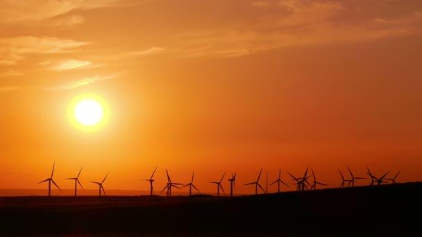Větrné turbíny na pozadí zlatého západu slunce.