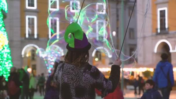 lisbon, portugal - 26.12.18: strassenkünstler kreiert große große seifenblasen für kinder, um spaß dabei zu haben, die seifigen transluzenten kugeln in die luft zu blasen.