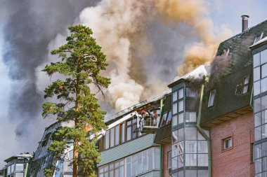 Moscow, Russia - August 26, 2018: Firefighters extinguish a fire by the top of the building.