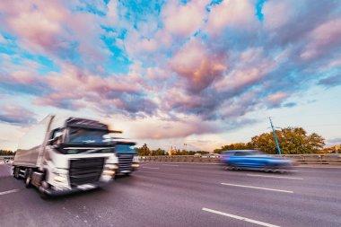 Yük kamyonu gün batımında otoyolda hızlı hareket ediyor.