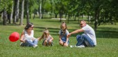 Happy young family have a rest in the park sitting on a grass