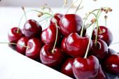 Friss lédús édes vörös édes cseresznye egy fehér kerámia tálban egy világos fából készült háttér. Az egészséges reggeli, snack-koncepció. Closeup a szelektív fókusz.