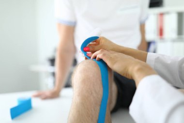 Knee joint of kinesiotape is fixed to patient in medical office.
