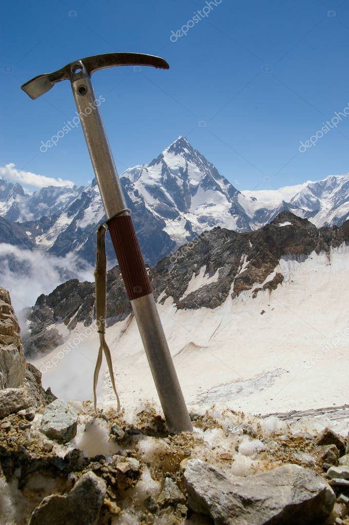 Ice ax against the backdrop of a mountain landscape