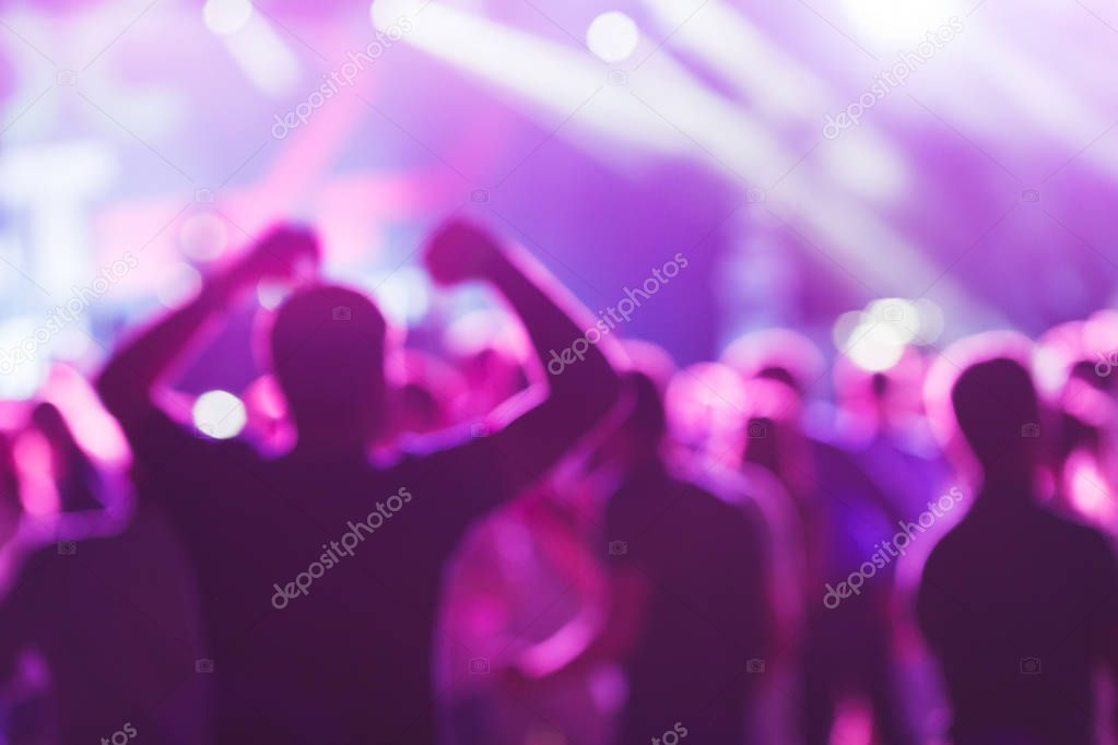 Bright colorful background with the silhouettes dancing young people during the performance favorite musician.