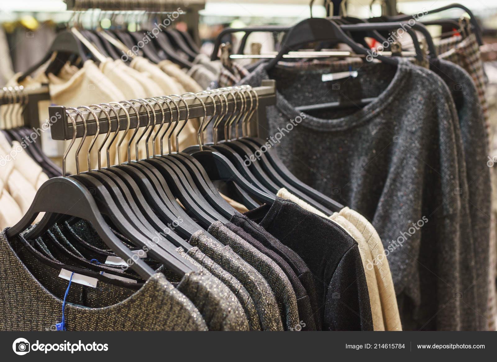 cb99843744 Μοντέρνα Αντρικά και γυναικεία ρούχα στις ξύλινες κρεμάστρες σε ένα  κατάστημα για μοντέρνα ρούχα — Φωτογραφία
