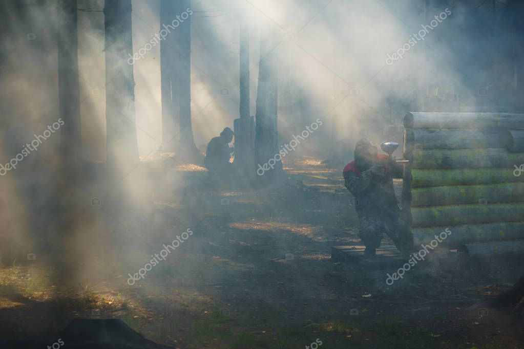 Playground in paintball with dramatic lighting and players during the game in special equipment and game markers.