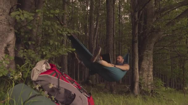 man working outdoors with laptop in hammock at sunset in the mountains