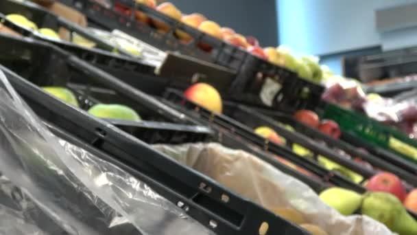 4k. Ultra HD. mladá Kavkazská žena vyzvedne jídlo z supermarketu, aby si je koupila. Mladá žena vybírá ovoce a zeleninu z obchodu s potravinami v supermarketu.