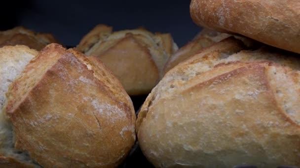 Posouvání z jezdce. Na stojanu plném chleba v pekárně si odpočiňte chléb různých druhů tmavé mouky. Na pozadí můžete vidět šedou zeď.