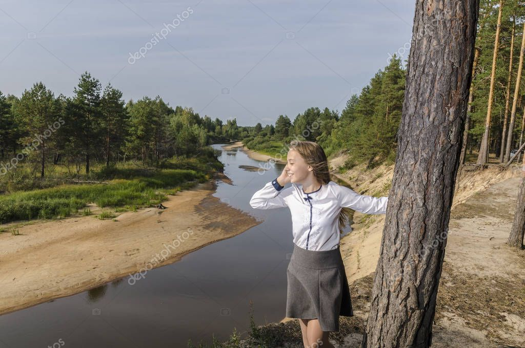 Girl talking on mobile phone standing on the high bank of the river