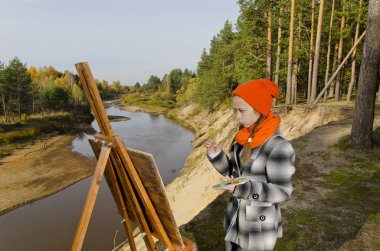 Girl painting a landscape.