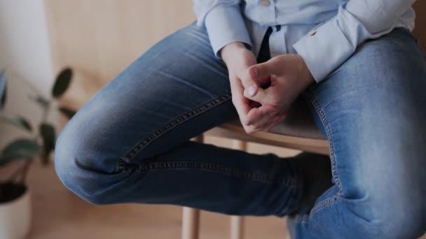 Kaukasier in Hemd und Jeans sitzt auf Holzhocker, gestikuliert mit den Händen