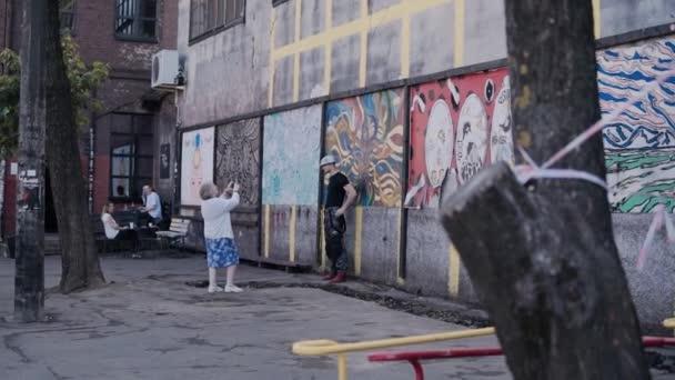 Starší žena fotí na smartphonu mladého chlapa ze zdi s kresbami