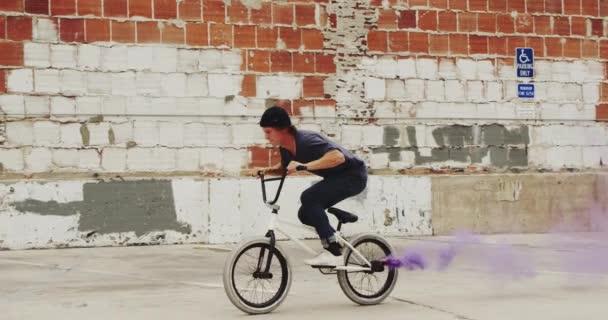 Extrémní biker Bmx dělá ocas bič s fialové barevné dýmovnice v pomalém pohybu