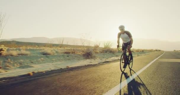 Mladý muž zpomalené činnosti na silničním kole venku na Pouštní silnici při západu slunce s odlesk objektivu
