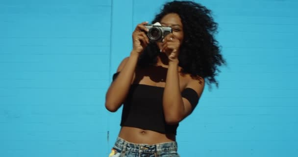 Slow motion shot of African American woman playing with film camera and taking photos