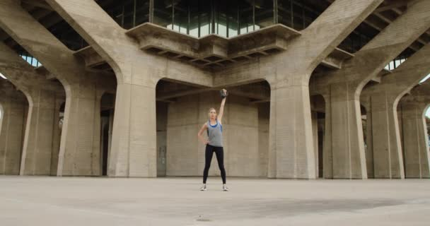 Young strong woman doing exercise with kettlebell under stone bridge