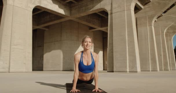 Young strong woman doing yoga exercise under stone bridge