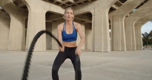 Young strong woman doing exercise with ropes