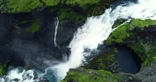 Top down aerial view of giant waterfall flowing in Iceland mountains filmed in slow motion