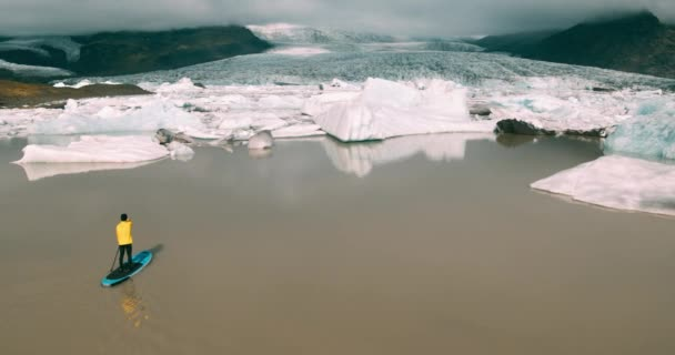 Aerial view of man wearing bright yellow raincoat paddling standing up on paddle board in glacier lagoon with giant icebergs in Iceland