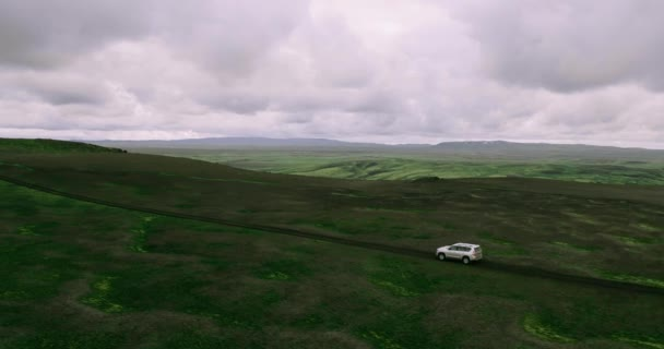 Aerial view of tracking shot of silver car driving on Iceland mountains road