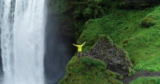 Man wearing yellow raincoat enjoying view of giant waterfall flowing in Iceland mountains