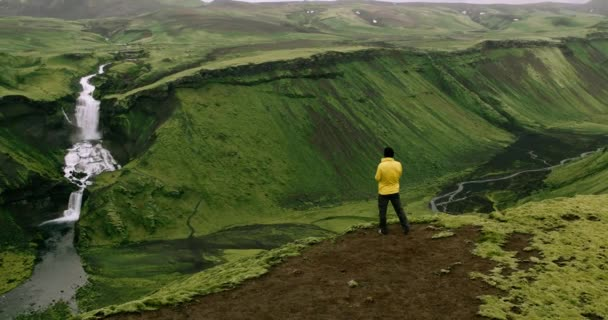 Man wearing yellow raincoat enjoying view of giant waterfall flowing in Iceland mountains