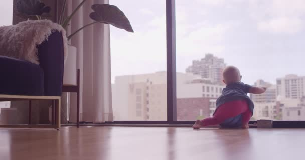 Young baby girl learning to stand in front of glass window in city apartment