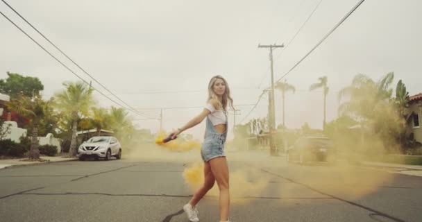 footage of beautiful young woman with colorful smoke on street