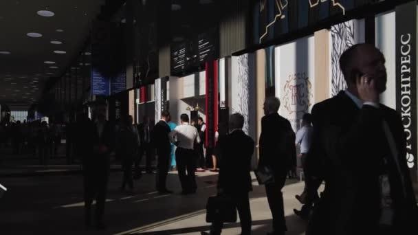 businessmen people walk around the exhibition hall in the shade and sunlight SPIEF Saint Petersburg International Economic Forum 2019 Expoforum