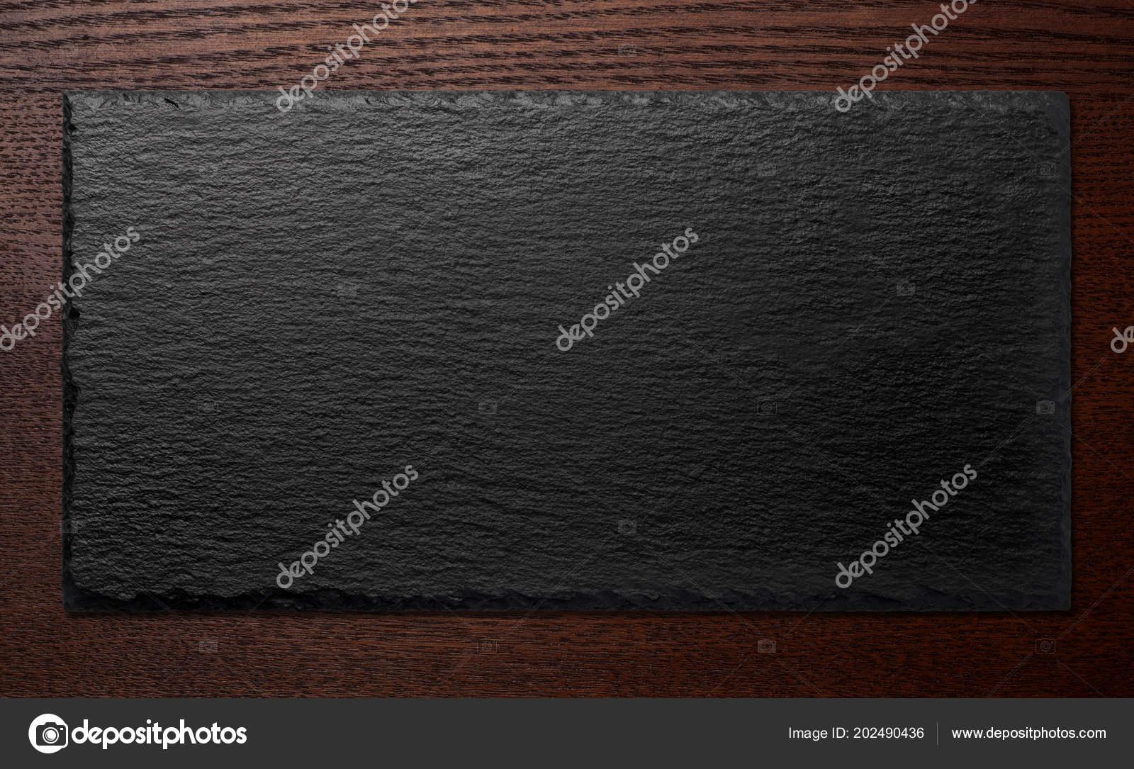 black stone plate wooden background stock photo koosen 202490436