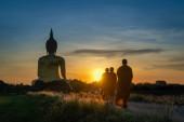 Angthong, Thailand - 28. Juni 2020: Mönche gehen Almosen um die Große Goldene Buddha-Statue mit Morgensonnenaufgang am Wat Muang Tempel, berühmter Ort der Religion wird in Thailand verehrt