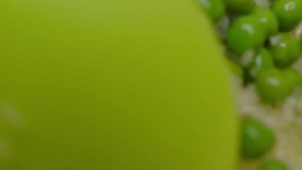 Nahaufnahme eines Löffels Reis mit grünen Erbsen verrühren