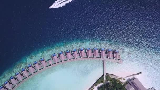 Reihe von Bungalows und Reitboot an der Küste der Malediven
