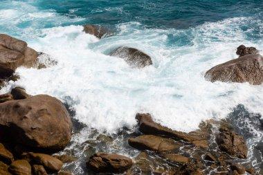 Big ocean splash near coast with rocks