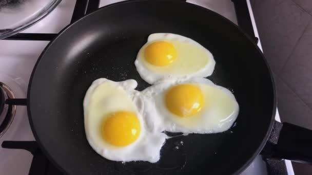 Három csirke tojás sült a vas serpenyőben.