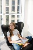 träumende Schulmädchen sitzen im heimischen Sessel mit Buch