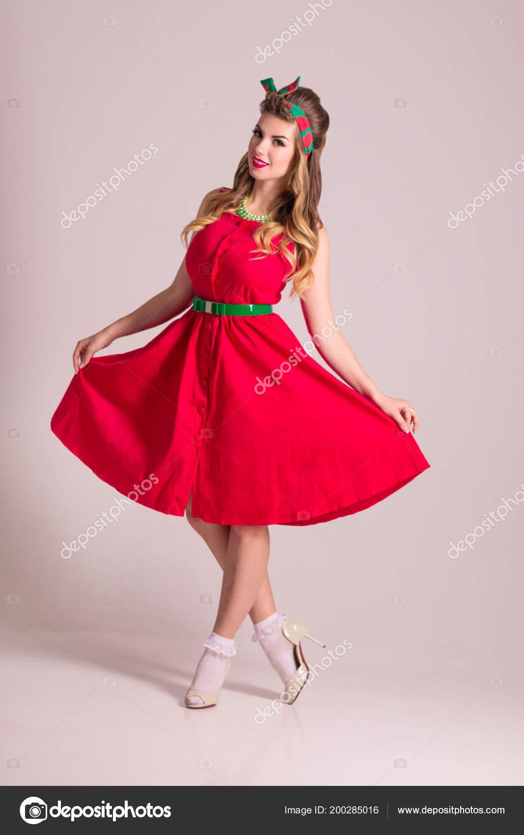 Mooie Rode Jurk.Mooie Vrouw Rode Jurk Met Kapsel Staat Grijs Studio Pin Stockfoto