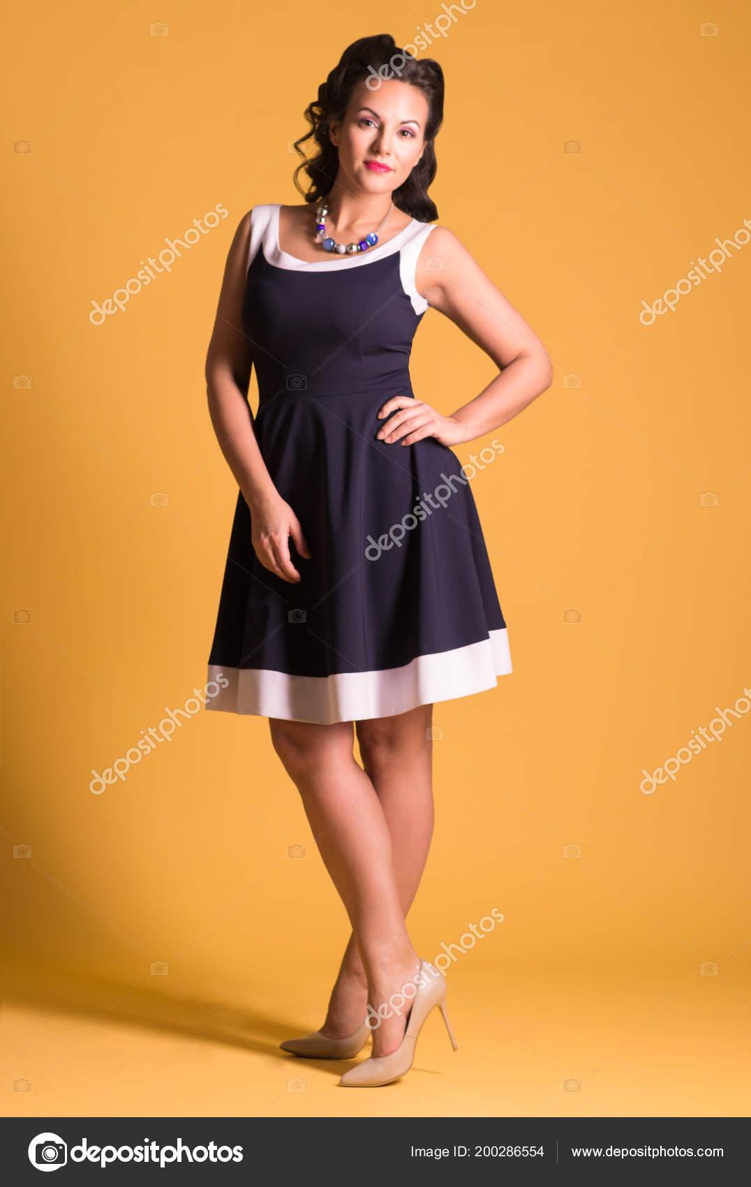 be69d9d7a75 Χαμογελαστή γυναίκα στο φόρεμα με κόμμωση στέκεται στο κίτρινο studio, pin  up στυλ, γεμάτο σώμα — Εικόνα από singulyarra1