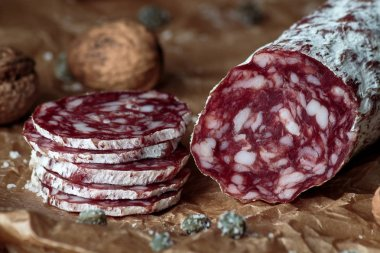 Italian salami with walnuts on craft paper on rustic  wooden backgroun