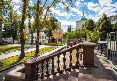 The Church of Cosmas and Damian in Stoleshnikov Lane of Moscow and the balustrade of the fountain, where pigeons bathe, on  a summer sunny morning