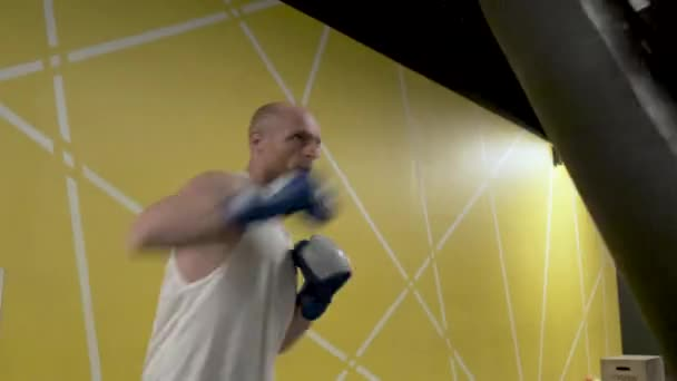 Young man punching boxing bag, professional athlete finishes active training. Stock footage