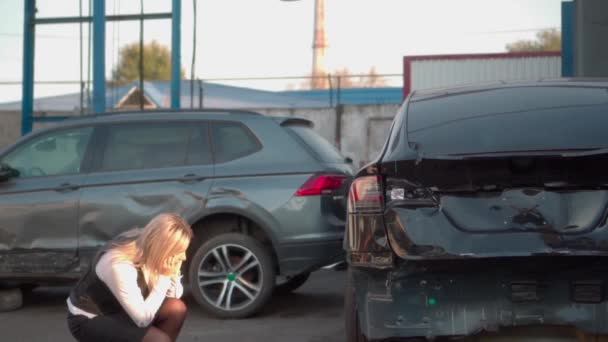 Upset girl near the broken car. Accident, a wrecked car, near which a girl is in despair. Strong feelings, tears. Damaged car at a car service center