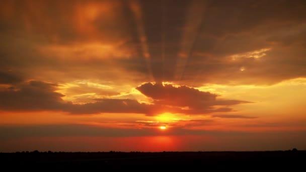 Zpomalený pohyb západu slunce. Paprsky se prodírají plovoucími mraky. Obloha má oranžové barvy. Dramatická scéna na obloze.