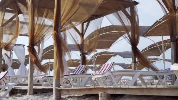 Leere Liegestühle für den Hotelurlaub. Der Wind schwingt die Vorhänge. Schutz vor der Sonne. Wellness-Behandlungen am Meer. Ein Ort zum Entspannen.