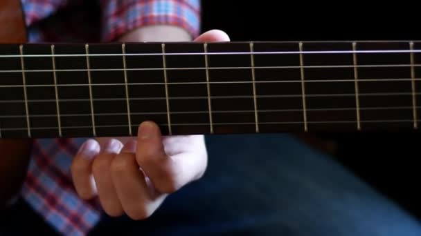 Boy learn how to play on classic guitar. Close up. Fingers touch the strings